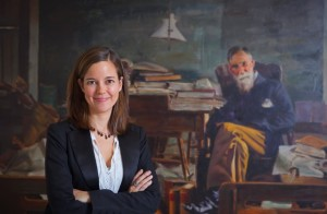 Alix Ohlin, associate professor of English, stands in front of a portrait painting of the late Lafayette English professors Francis A. March