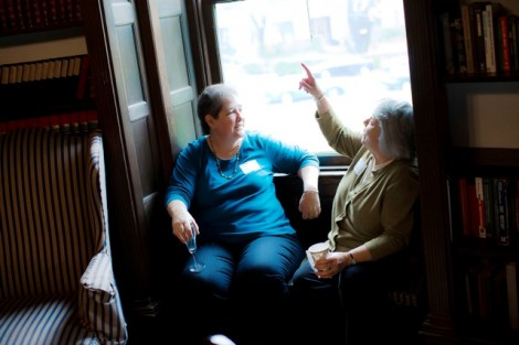 Laura May '72, left, enjoys a conversation on a window seat in the library.