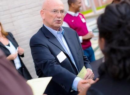 David Reif '68, president of the Alumni Association, greets attendees.