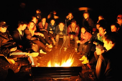 The class gathers around the campfire to reflect on a day of hiking.
