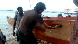 Yen Joe Tan '14 helps with the staining of a dhow boat while studying abroad in Kenya.