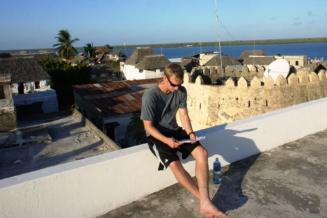 Robert Bedson '13 reads an article about Swahili history on a rooftop in Lamu town.