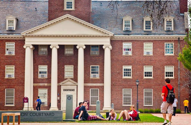 Students relax on Anderson Courtyard with Watson Hall in the background.