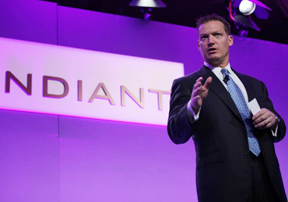 Kevin Mandia '92 speaks before an audience with his company's name, Madiant, in the background
