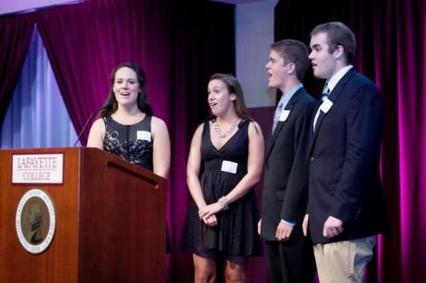 Students Allie Shumeyko '14, Maddie Zufschnitt '17, Mac Jones '16, and Adam Kline-Schoder '17 lead the dinner attendees in singing the 'Alma Mater.'