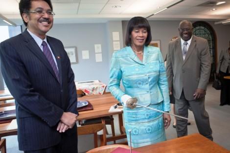 Jamaican Prime Minister Portia Simpson Miller handles the sword of Marquis de Lafayette as Stephen Vasciannie, Jamaican ambassador to the U.S., watches.