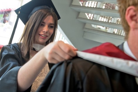 Graduating seniors put on their robes and prepare for the ceremony in Kirby Sports Center.