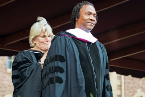 Nancy Kuenstner '75, secretary of the Board of Trustees, presents Roger Ross Williams with the hood emblematic of his honorary Doctor of Arts degree.