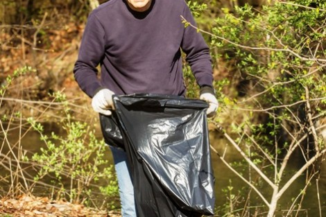 David Neff '69 picks up trash along the Karl Stirner Arts Trail.