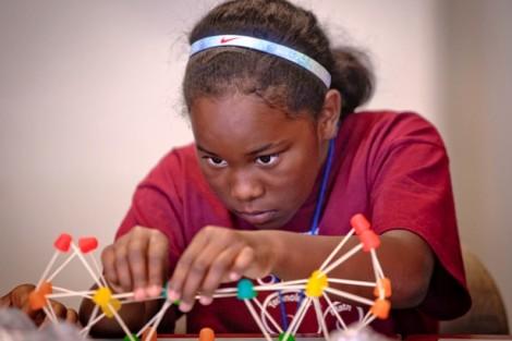 Campers construct toothpick bridges.