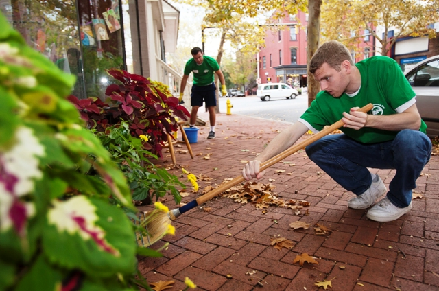 Connor Heinlein '15 sweeps up in front of the Journey Home building on Second Street.