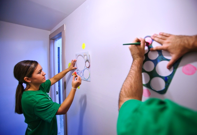 Caroline Bitterly '17 uses stencils to paint designs on a wall in the Journey Home building.