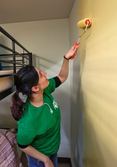 Basmah Raja '15 puts a fresh coat of paint on a wall in Easton's Safe Harbor homeless shelter.