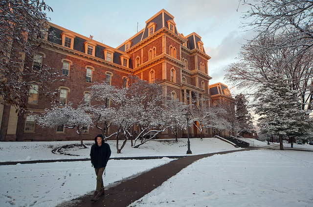 A student walks by Pardee Hall as the sun sets.