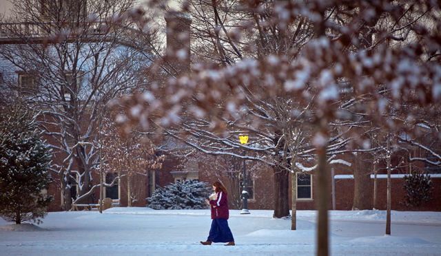 A student crosses the Quad near Kirby House.