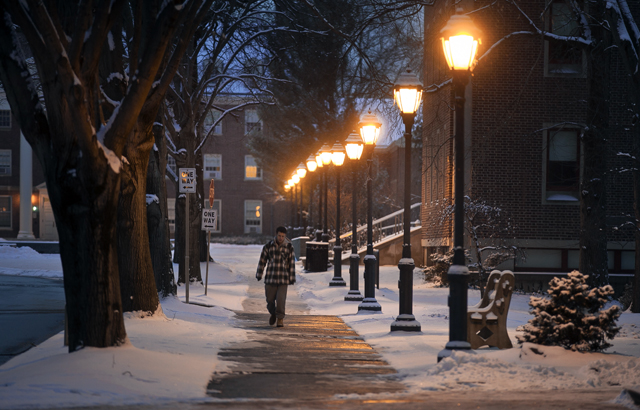 A student makes his way past Markle Hall in the early evening.
