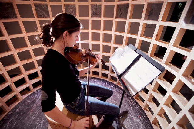 While seated in a large cage, Joanna Harris '17 plays viola.