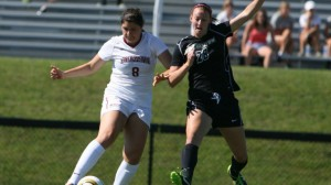 Caroline Craver '15 kicks the soccer ball while shielding it from a defender.