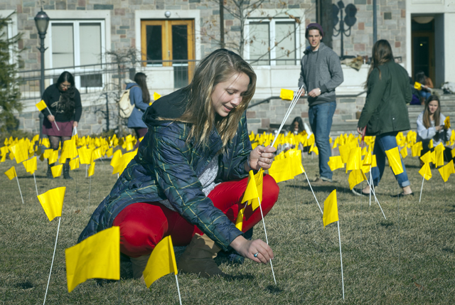 Robyn Henderek '15 plants flags in the ground.
