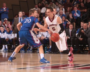 Joey Ptasinski dribbles the ball while an American University player defends.