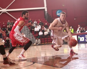 Nick Lindner dribbles the basketball while defended by a Boston University player