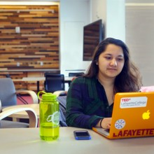 Nirupa Basnet '17 takes advantage of one of the new study rooms. Wooden panels, like the one behind her, are featured throughout the building. The use of salvaged lumber from around the world in the center promotes local and recycled materials and reflects the global focus.