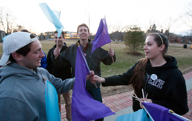 Rebecca Miller '16 hands out flags before the march.