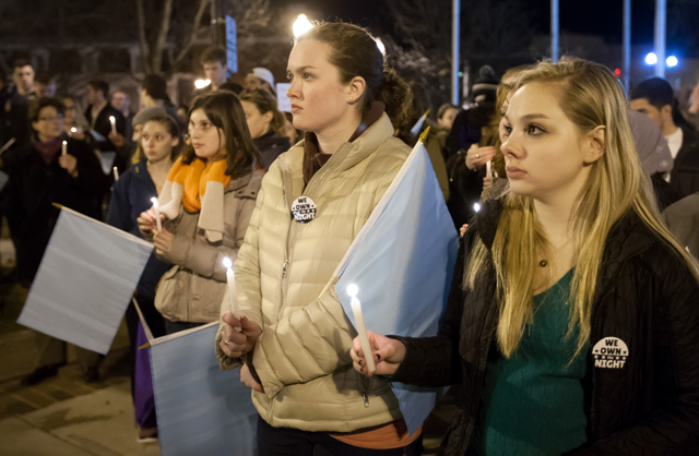 Kaitlin Kinsella '17 and Emma Smith '17 hold candles in support of victims of sexual violence.