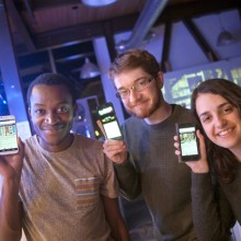 Raymond Macharia '15, Louis Wheeler '15, and Ellen Galperin '15 show off the Frankenstein 2029 mobile website on the set of the production.