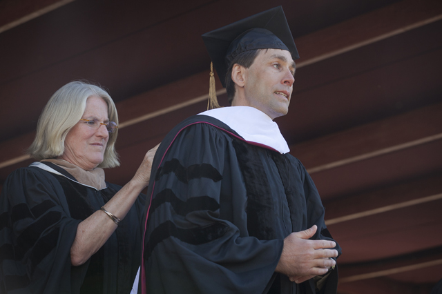 Nancy Kuenstner '75, secretary of the board, presents Erik Weihenmayer with the hood emblematic of his honorary Doctor of Humane Letters degree.