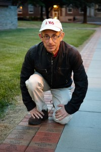 Robert Singer '65 poses with his Fleck Society brick on the Quad.