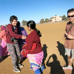 A Lafayette student shakes hands with an Indian woman while another student stands nearby with camera in hand