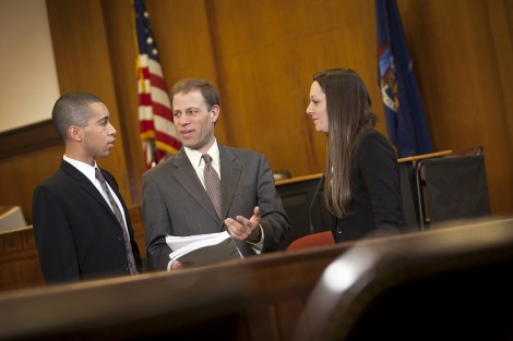David Hammer, Manhattan Assistant District Attorney, goes over a brief prior to a court hearing with Robert Sanchez '16 and Jennifer Minervini '15.