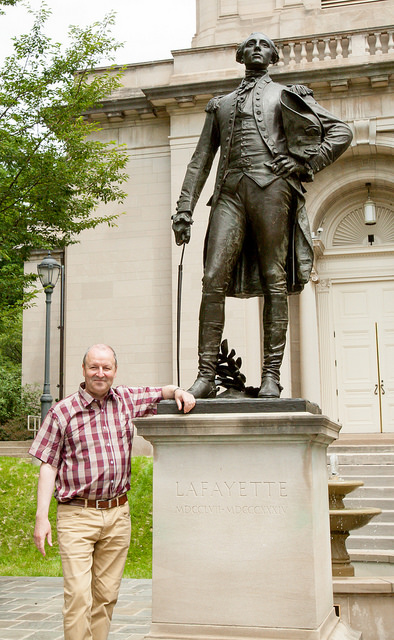 La Fayette stands by the statue of his ancestor.