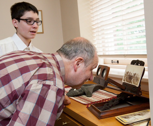 La Fayette and his son Alexander examine historical photos in the President's Office.