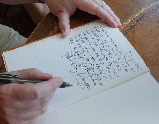 The Comte signs the guest book at the Chateau Chavaniac.