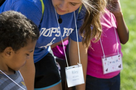 A camper shows Riley Godshall '19 how he decorated his nametag.