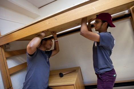 Resident assistants help raise a bed in McKeen Hall.