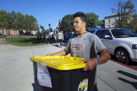 Football player Izaiah Avent '19 carries another student's items into Ruef Hall.