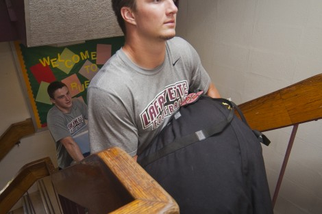 Football player Michael Root '18 carries a first-year student's gear into Ruef Hall.
