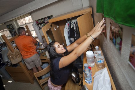 Shreya Nebhwani '19 hangs photos on her wall in Ruef Hall.