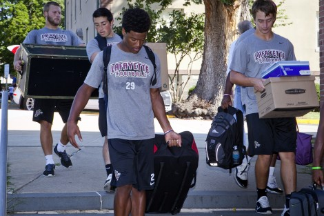 Kaizer Butler '19 and other football players help with the move in.