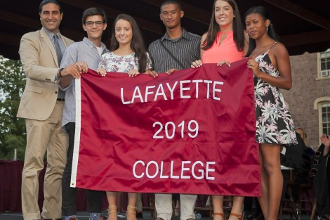 Alex Karapetian '04, president of the Alumni Association, presents the students with the Class of 2019 banner.