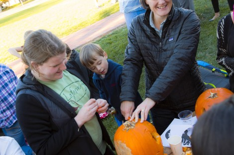 Haley Mauriello '18 and Professor Kira Lawrence clean out a pumpkin with Lawrence's son Kai.