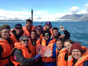 Students on the Iceland interim course pose with an ice chuck from a glacier.