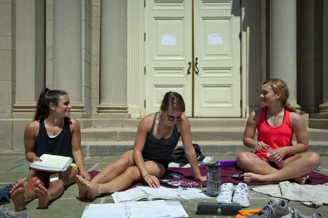Students get some work done in the sun on the steps outside Colton Chapel.
