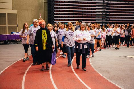 A crowd of mostly students walks around the indoor track at Relay for Life.