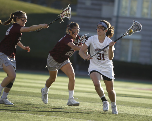 Kirsten Wilhelmsen '17 runs with the ball in her stick while being defended by Colgate players in a women's lacrosse game