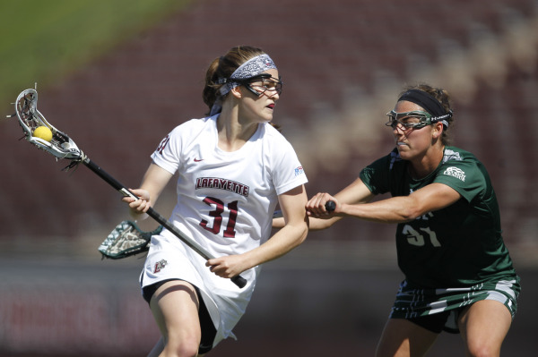 Kirsten Wilhelmsen '17 carries the ball in her stick during a women's lacrosse game against Loyola.
