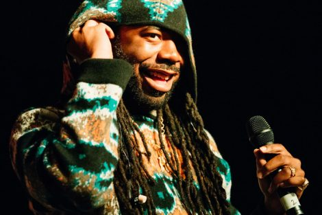 Rapper DRAM smiles while holding the microphone.